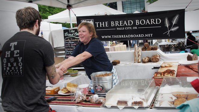Sally Cruckshank, an employee with The Bread Board bakery and cafe in Falls City, helps a customer at the Salem Saturday Market on May 16.