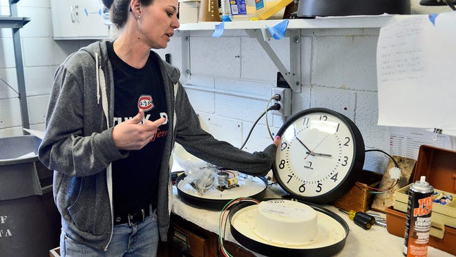 St. Cloud State University maintenance electrician Alyssa Heinen shows some of the extra clocks in the storage and repair  room Oct. 21 . SCSU uses a mix of clocks, about half of which are made by the Dassel company American Time. American Time's clocks are synchronized wirelessly on a regular basis from a signal broadcast from Centennial Hall, including when daylight saving time changes occur.