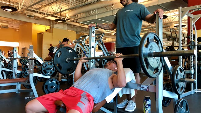 Evolutions gym member, Ray Hernandez, works out while his friend and Evolutions employee Derrick Austin spots him.