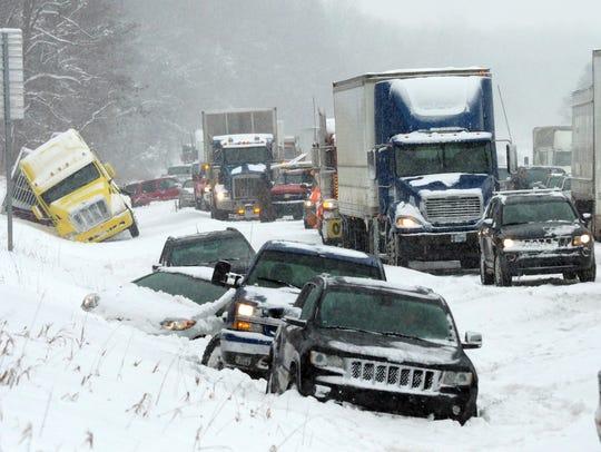 Vehicles rest along the snowbound shoulder along Interstate