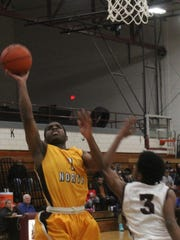 North Farmington senior Kamon McNear (1) drives to the hoop Thursday against Hazel Park.