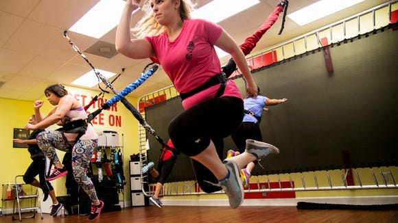 Emily Underwood does a running jump attached to a bungee cord during a workout class at P2 Personal Training on Wednesday, July 5, 2017, in Cape Coral. The bungees take pressure off joints and allow for a fun workout. (Amanda Inscore/The News-Press)