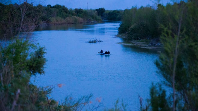 Border crossers paddle across the Rio Grande from Mexico (right) to Rio Grande City, Texas, earlier this month. They were turned back by Border Patrol helicopters.