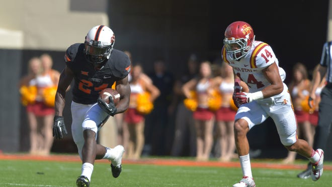 Oklahoma State's Tyreek Hill (24) returns a kick as Iowa State's  Jared Brackens (14) tries to catch him.