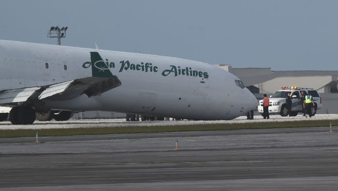 An Asia Pacific Airlines plane rests on the Guam international Airport runway after making an emergency landing without front landing gear deployed on Feb. 26.