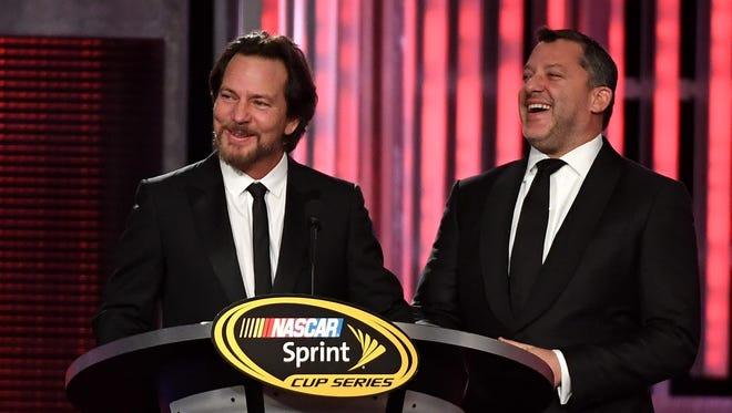 Pearl Jam singer Eddie Vedder, left, honors retiring NASCAR driver Tony Stewart Friday in Las Vegas.