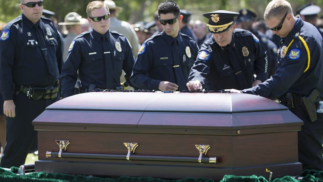 Law enforcement leave their shroud badge on the coffin of Phoenix Officer David Glasser as he is laid to rest at Phoenix Memorial Park and Cemetery in Phoenix on May 26, 2016.