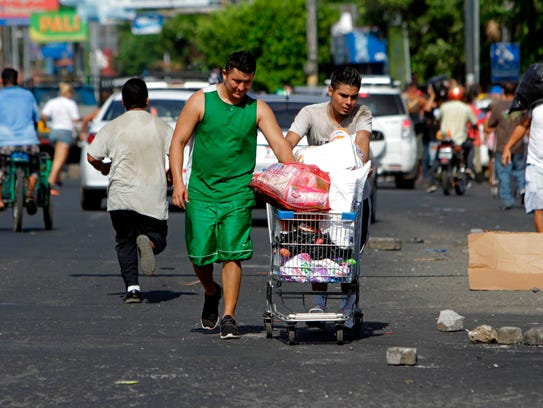 People push carts with goods after looting a supermarket