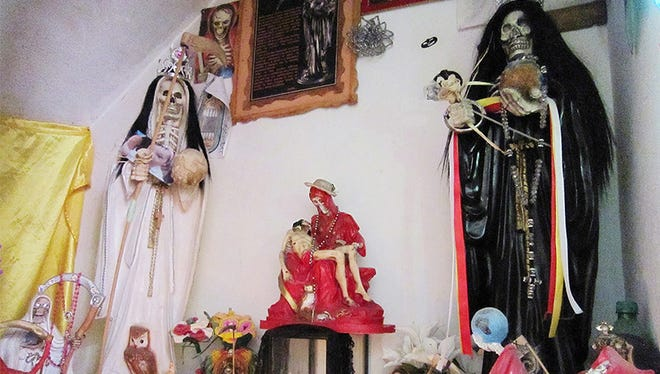 A shrine to Santa Muerte kept in the house of Betzy Ballesteros in Guadalajara, Mexico. The shrine includes statues, candles, candy and photos of several of Ballesteros' transgender friends who were murdered and abandoned.