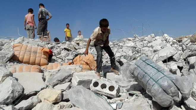 People stand on the debris of a damaged home after U.S.-led coalition airstrikes  Sept. 23 in Kfar Derian, Syria.
