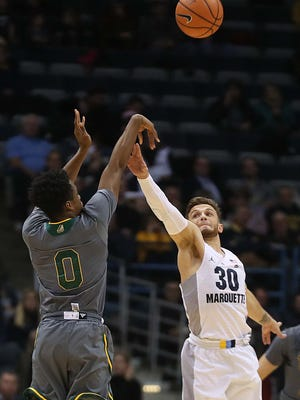 Vermont Catamounts guard Stef Smith (0) hits a three pointer against Marquette Golden Eagles guard Andrew Rowsey (30) and ended the night with 20 points during Marquette's  91-81 win over Vermont  in the men's basketball game at the BMO Harris Bradley Center in Milwaukee, Wisconsin, Tuesday, December 05, 2017.  Milwaukee Journal Sentinel photo by Rick Wood/RWOOD@JOURNALSENTINEL.COM