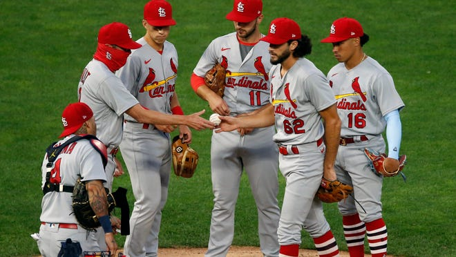 Cardinals pitcher Daniel Ponce de Leon hands the ball over to manager Mike Shildt, left, after being pulled in the fifth inning of the team's game Wednesday night against the Twins in Minneapolis.