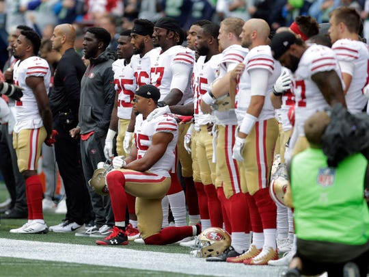 San Francisco 49ers strong safety Eric Reid kneels during the singing of the national anthem before an NFL football game against the Seattle Seahawks, Sunday, Sept. 17, 2017, in Seattle.