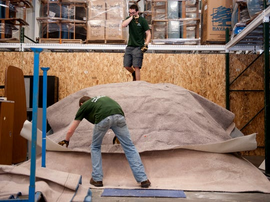 Ross Hunter, on the carpet pile, and Brad Petty sift through carpet left behind in the dorms at the MSU Surplus Store and Recycling Center in East Lansing on Friday, May 13, 2016. Anywhere from 70-80,000 pounds of carpeting was left behind.