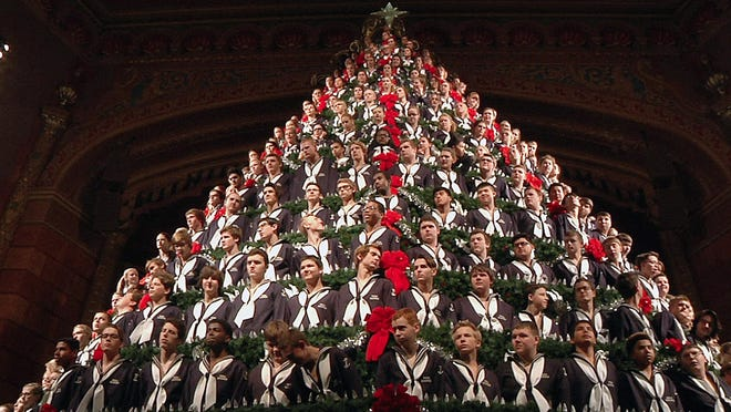In this Wednesday photo, members of the Mona Shores High School Choir stand in the Singing Christmas Tree during a dress rehearsal performance at the Frauenthal Center in Muskegon, Mich. The five-story Singing Christmas Tree features 15 tiers on which about 220 student singers stand.
