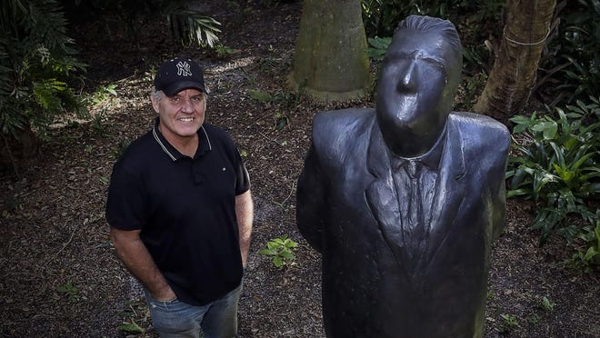 "Artist Jim Rennert stands near his sculpture ""Perspective"" at the Ann Norton Sculpture Gardens in West Palm Beach, where ""With These Hands: Sculptures by Jim Rennert"" is on view."