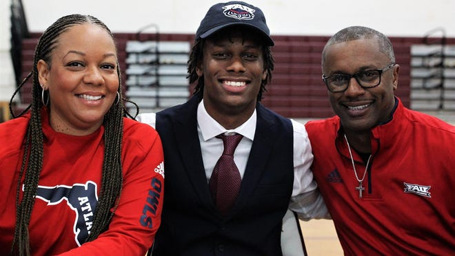 Florida High quarterback Willie Taggart Jr., center, celebrates signing with Florida Atlantic alongside mother Taneshia and father Willie Taggart, who is FAU's new head coach.