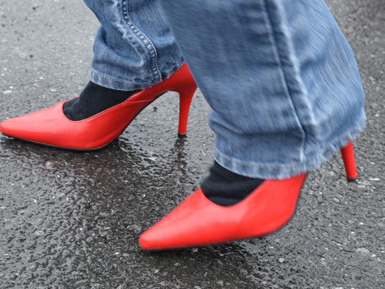 Men try on pumps in preparation for the Walk in her