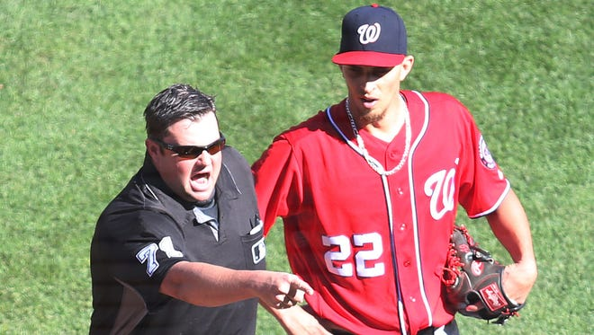 Home plate umpire Jordan Baker (71) reacts to the Nationals dugout after ejecting Washington pitcher A.J. Cole (22) against the Pittsburgh Pirates.