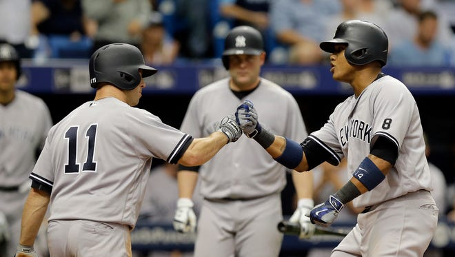 New York Yankees' Starlin Castro, right, celebrates his two-run home run off Tampa Bay Rays starting pitcher Jake Odorizzi with teammate Brett Gardner, left, during the seventh inning of a baseball game Sunday, May 29, 2016, in St. Petersburg, Fla.
