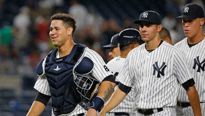 A smiling New York Yankees catcher Gary Sanchez, left, leaves the field with teammates Ben Heller, center, and right fielder Aaron Judge, right, after the Yankees defeated the Baltimore Orioles 14-4 in a baseball game in New York, Friday, Aug. 26, 2016.