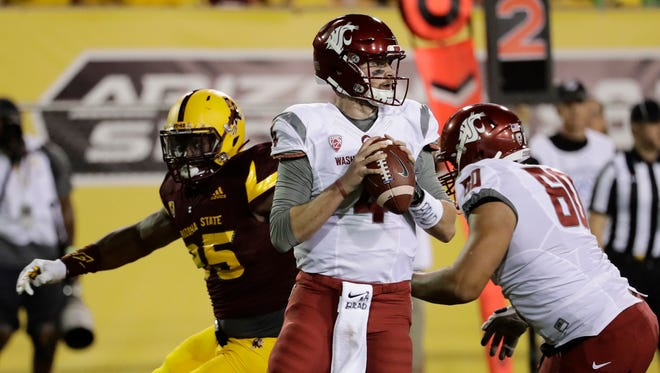 Washington State quarterback Luke Falk (4) looks to throw under pressure from Arizona State defensive lineman Renell Wren (95) during the first half of an NCAA college football game, Saturday, Oct. 22, 2016, in Tempe, Ariz.