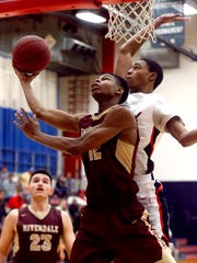 Riverdale's Elijah Cobb (12) goes up for a shot as Oakland's DD Anderson (23) defends him on Friday.