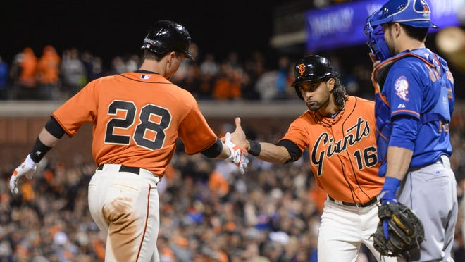 San Francisco Giants catcher Buster Posey (28) and center fielder Angel Pagan (16) celebrate after both scored on a two-run home run by Posey as New York Mets catcher Travis d'Arnaud (right) looks on during the eighth inning Friday at AT&T Park.