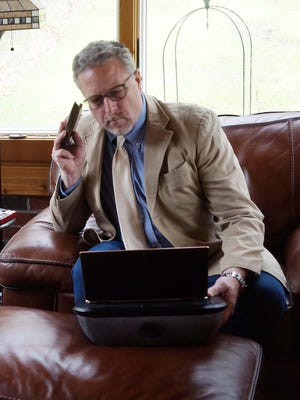 John Petit, managing attorney for Community Legal Aid's housing programs, talks with a client while working remotely during the coronavirus pandemic.