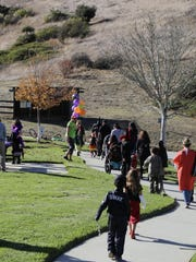 A variety of costumes, including a SWAT team member, walk along the path.