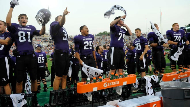 Northwestern Wildcats players cheer on their team against the Syracuse Orange during the third quarter at Ryan Field.
