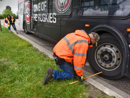 Workers measure the distance of a bus to the curb on