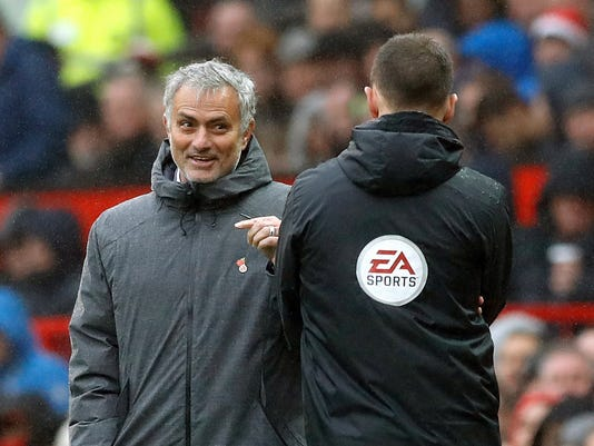 Manchester United manager Jose Mourinho, left, exchanges words with fourth official Stuart Attwell during the game against Tottenham Hotspur, during their English Premier League soccer match at Old Trafford in Manchester, England, Saturday Oct. 28, 2017. (Martin Rickett/PA via AP)