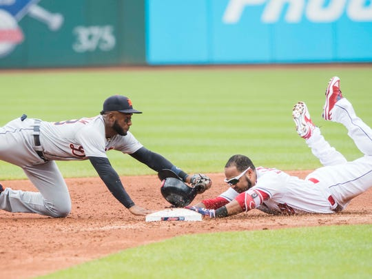 Indians designated hitter Edwin Encarnacion slides into second base for a double before the tag of Tigers second baseman Niko Goodrum during the first inning June 24, 2018, in Cleveland.