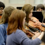 Students play violins Thursday during orchestra class at Richmond High School.