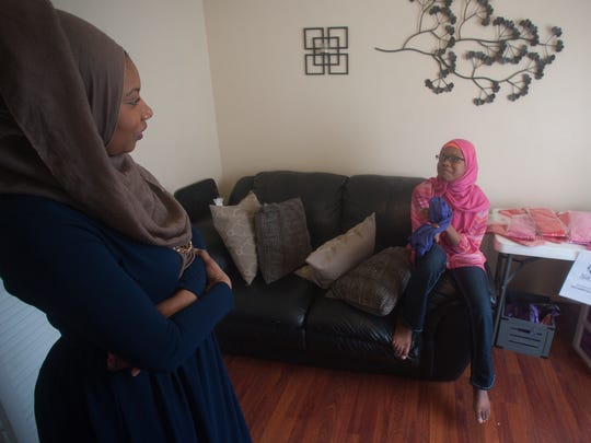 Amaya Diggins, 10, right, talks with her mother, Ameenah Muhammad-Diggins at her home in Willingboro. The Muslim girl started her own business making hijabs for teens and tweens.