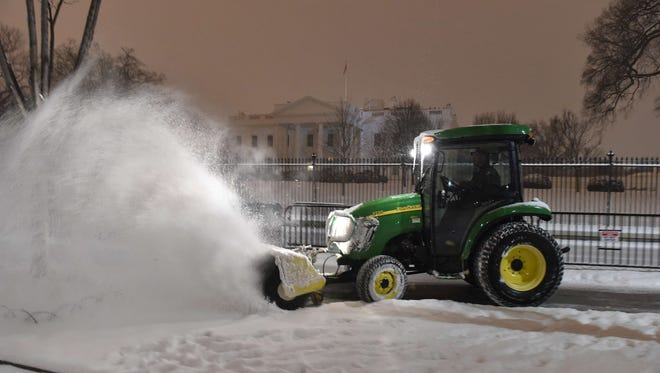 Snow is cleared on Pennsylvania Avenue in front of the White House late Monday.