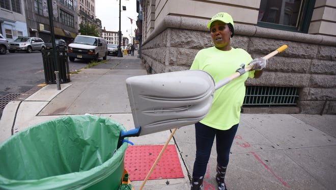 """""""Paterson was once a beautiful city and we need to show the young people that it can be again,"""" said Evetta Thomas, 55, shown working near the corner of Church and Ellison streets in Paterson on 09/12/18. Paterson has given temporary, part-time jobs paying $14.42 to 17 people to clean the streets in about 29 different commercial strips."""