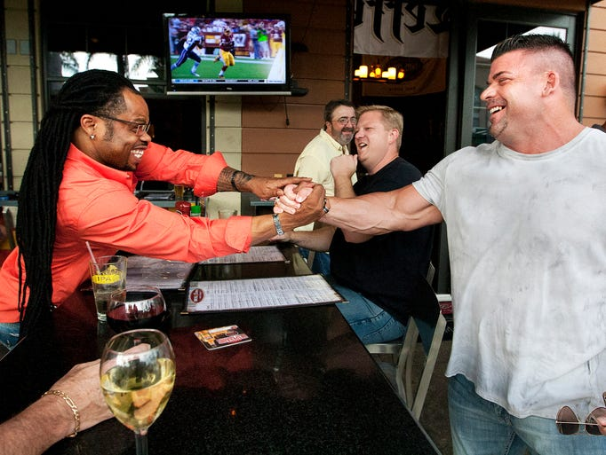 """Look at you,"" exclaims Quincy Sorrell, left, to Steve Gorrie, right, during a reunion recently of the 2004 Florida Firecats at House of Brewz in Fort Myers."