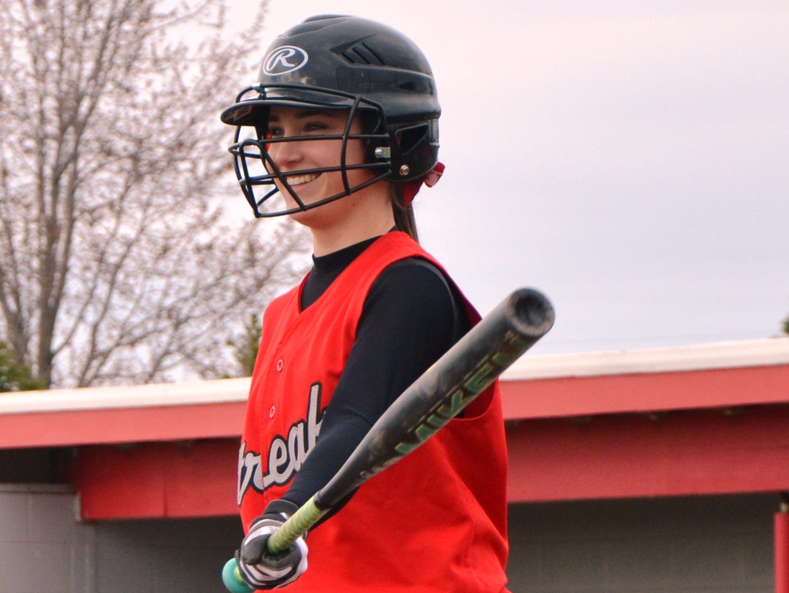 St. Joseph Central Catholic senior Josie Weickert smiles during an at-bat in SJCC's softball game against Clyde High School on Monday. Weickert is playing softball following two injuries to her right knee in the last three years.