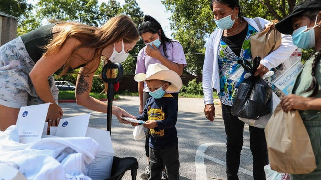 Volunteer Maggie Becker hands a mask to Jonathan Torres, 3, as his family members look on Saturday in East Austin. Halo Life and Hearing the Homeless distributed reusable masks to needy individuals.