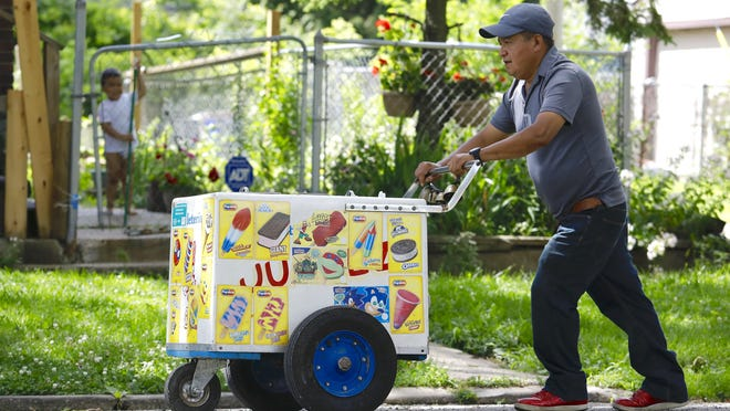 A child watches as Pablo Arroyo Perez pushes a cart full of paletas and other ice cream treats on Sunday, July 12, 2020, on Sanford Street in Rockford.