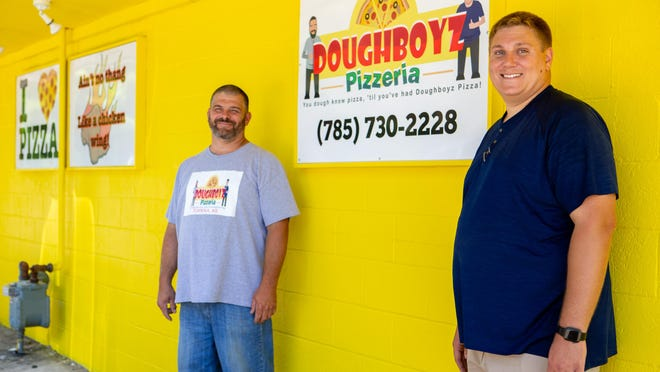 Doughboyz Pizzeria owners Eli Campbell, left, and Trevor Burdett stand outside their restaurant as construction continues to take place. The restaurant is set to open in mid-July at 1312 N. Kansas Ave.