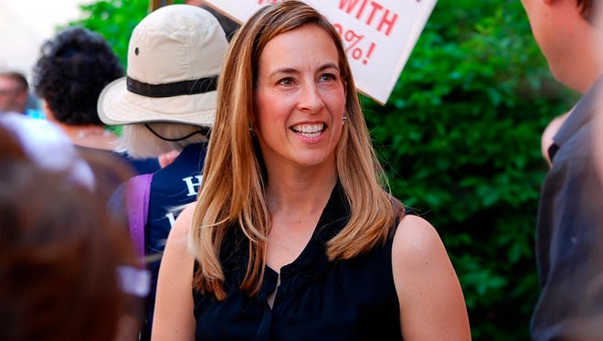 In a Friday, May 19, 2017 photo, Mikie Sherrill joins protesters with NJ 11th for Change outside of U.S. Rep. Rodney Frelinghuysen's Morristown office. Sherrill is running in New Jersey and said she hasn't found anyone in her district who doesn't agree that the goal should be quality and affordable health care for everyone.