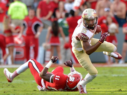 Travis Rudolph #15 of the Florida State Seminoles breaks away from Juston Burris #11 of the North Carolina State Wolfpack during their game at Carter-Finley Stadium on September 27, 2014 in Raleigh, North Carolina. Florida State won 56-41.