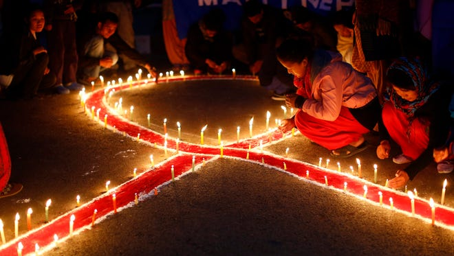 A group of women and children of 'Maiti Nepal', a Rehabilitation and Orphanage home for HIV-affected children and women who are victims of trafficking, attend a candle light prayer meeting on the eve of World AIDS Day in Kathmandu, Nepal.