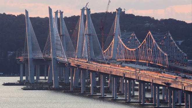 The sun rises as early morning drivers cross the Gov. Mario M. Cuomo bridge, driving westbound toward Rockland County, alongside the Tappan Zee Bridge.