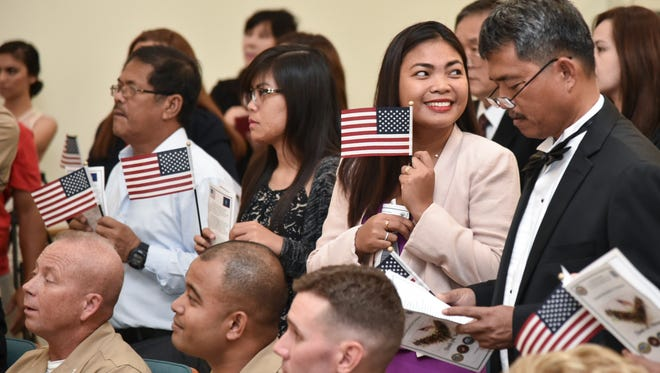In this Nov. 10, 2016, file photo, new citizens from American Samoa, the Philippines and South Korea, were sworn in during a naturalization ceremony at the University of Guam.