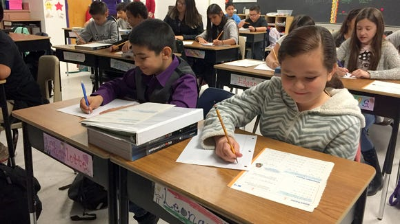 Fifth-grade students work on math problems at O'Shea Keleher Elementary School.