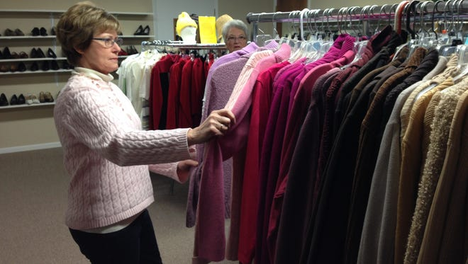 Donna Schweihofer and Jackie Rands arrange  clothing on a rack at The Thrift Shop in St. Clair.